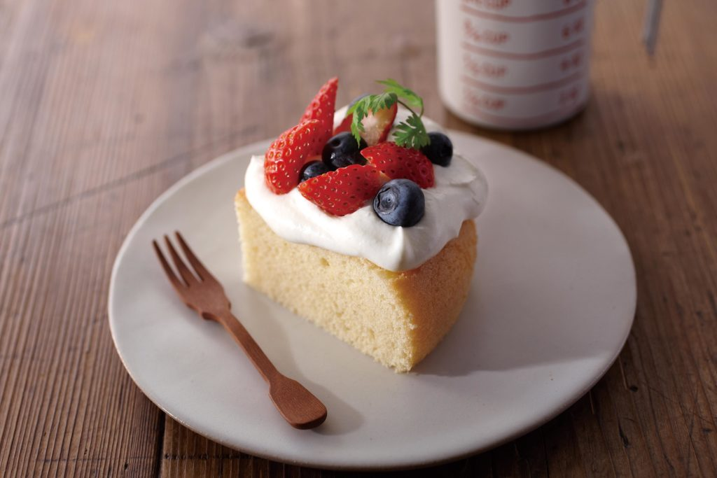 Slice of rice cooker sponge cake with whipped cream and berries