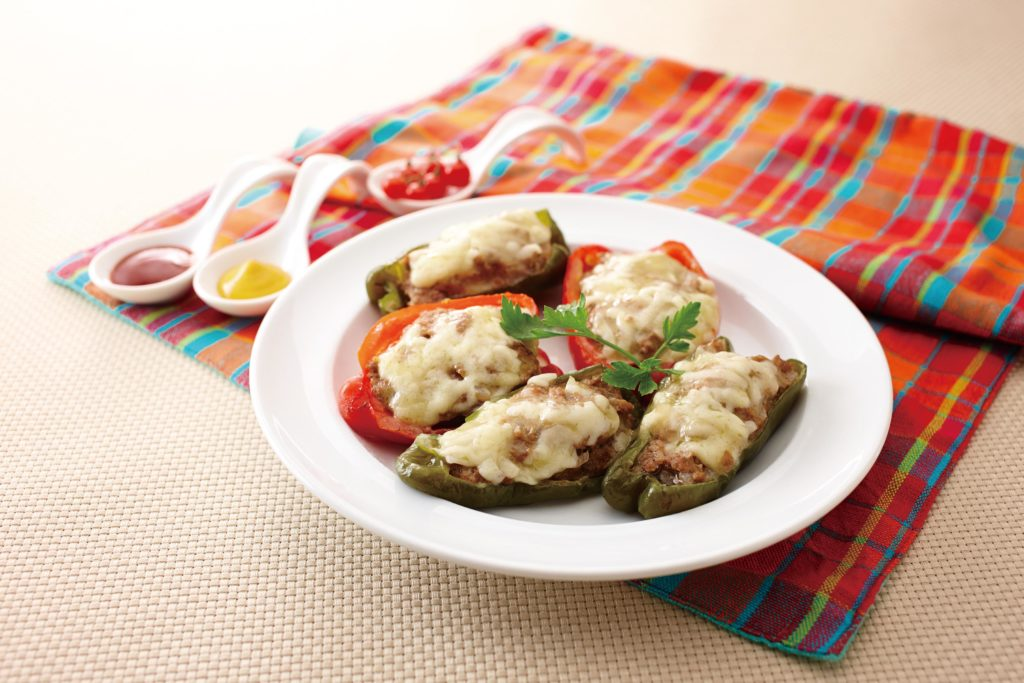 Stuffed Bell Peppers - These yummy stuffed bell peppers are brimming with a savory mixture of ground beef and pork. Onions and milk-soaked bread crumbs keep the interior moist. The whole things is topped with delicious ooey-gooey melted cheese. #sidedish #stuffedpeppers #groundbeefrecipe | Tiger USA